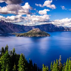 A Large Mountain In The Background With Crater Lake National Park In The Background