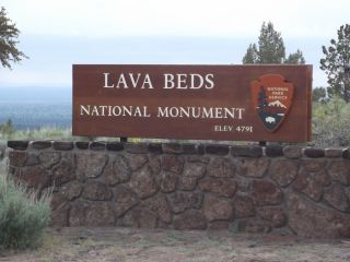 A Sign In Front Of A Large Rock