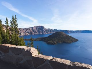 A Rocky Island In The Middle Of A Snow Covered Mountain With Crater Lake National Park In The Background